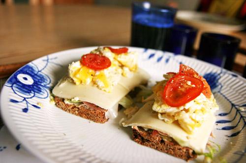Rugbrød med romaine salat, serrano skinke, lagret ost, scrambled eggs og cherrytomat
